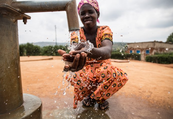 A WaterAid trained pump mechance and local leader, Gaudence Mukahabyarimana, washes her hands at the handpump in Nkange, Rwanda, February 2018. Credit: WaterAid/ Jacques Nkinzingabo