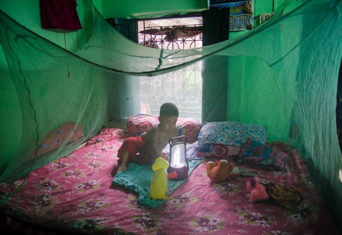 A boy, aged two, plays inside a mosquito net in Kolkata, West Bengal, India. Photo: Sudip Maiti