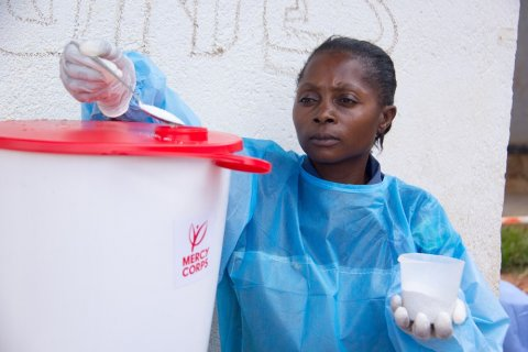Beni, North Kivu, DR Congo. Kavira Safari Esperance, a hygienist at the Malepe Health Center, has attended the Mercy Corps promoted hygiene awareness outreaches against Ebola. She is using chlorine to disinfect the water used to wash hands. © Mercy Corps