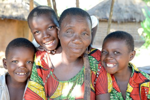 Berthine (64) is blind due to onchocerciasis, with her grandchildren. DRC. CBM/Tobias Pflanz