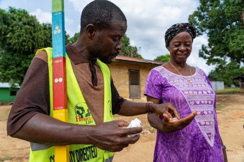 Community Volunteer Victor Scott gives Hawa Barclay treatment to protect her against onchocerciasis in Gbarpolu Liberia. Photo: Sightsavers/ Carielle Doe
